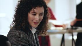 Närbildstående av den lyckliga attraktiva unga europeiska affärskvinnan som ler, lyssnar och nickar på det moderna kontoret stock video