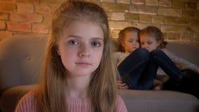 Närbildstående av den nätta caucasian flickan som i stillhet håller ögonen på in i kamera med hennes systrar på bakgrund lager videofilmer