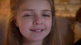 Närbildstående av den nätta caucasian flickan som smilingly håller ögonen på in i kamera med hennes systrar på bakgrund lager videofilmer