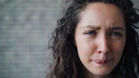 Närbildstående av den olyckliga unga flickan som gråter på bakgrund för tegelstenvägg stock video
