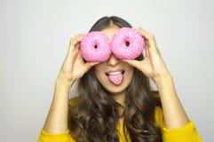 Närbildstående av den roliga le flickan med donuts som isoleras på grå bakgrund långt kvinnabarn för attraktivt hår Arkivbild