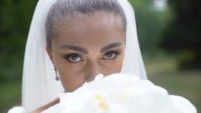 Närbildstående av den unga attraktiva brunettbruden som luktar bröllopbuketten av vita blommor och in ser arkivfilmer