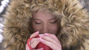 Närbildstående av den unga caucasian flickan med koppen av varm drink och smilingly att hålla ögonen på in i kamera på vintergata lager videofilmer