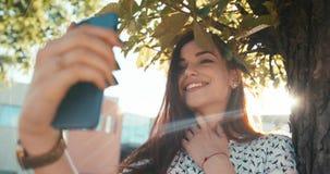 Närbildstående av den unga härliga brunetten med nätt leende och naturliga sminket som tar selfie på mobilen lager videofilmer
