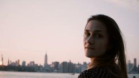 Närbildstående av den unga härliga europeiska flickan som ser solnedgång som poserar därefter på kameran nära storstadfloden 4K stock video