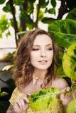 Närbildstående av den unga härliga flickan med sommarklänningen för lockigt hår i tropisk skog Arkivfoto