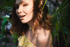 Närbildstående av den unga härliga flickan med sommarklänningen för lockigt hår i tropisk skog Arkivbild