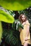 Närbildstående av den unga härliga flickan med sommarklänningen för lockigt hår i tropisk skog Fotografering för Bildbyråer