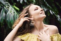 Närbildstående av den unga härliga flickan med sommarklänningen för lockigt hår i tropisk skog Arkivfoton