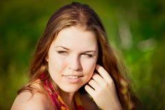 Närbildstående av den unga kvinnan med långt rött hår Royaltyfri Foto