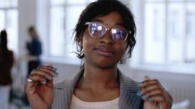Närbildstående av den yrkesmässiga unga afrikanska chefaffärskvinnan som justerar glasögon som poserar på det moderna kontoret stock video