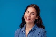 Närbildstående av en attraktiv brunettflicka med långt lockigt hår som poserar på en blå bakgrund fotografering för bildbyråer