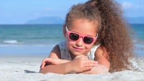 Närbildstående av en härlig liten flicka i rosa exponeringsglas, gulligt le se kameran som förbi ligger på sanden stock video