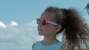 Närbildstående av en härlig liten flicka i rosa exponeringsglas, gulligt le som ser den blåa himlen Begrepp: Barn stock video