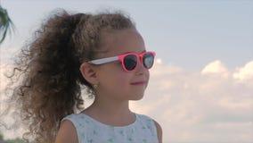 Närbildstående av en härlig liten flicka i rosa exponeringsglas, gulligt le som ser den blåa himlen Begrepp: barn arkivfilmer