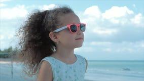 Närbildstående av en härlig liten flicka i rosa exponeringsglas, gulligt le som ser havet Begrepp: Barn lager videofilmer
