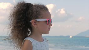 Närbildstående av en härlig liten flicka i rosa exponeringsglas, gulligt le som ser havet Begrepp: Barn arkivfilmer