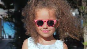 Närbildstående av en härlig liten flicka i rosa exponeringsglas, gulligt le som ser kameran Begrepp: Barn arkivfilmer