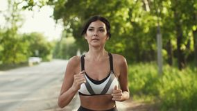 Närbildstående av en idrottsman nen Flickaspringen längs vägen på solnedgången Ung kvinna som gör sportar i natur långsamt stock video
