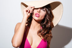 Närbildstående av en sexig strandflicka i hatt Arkivfoto