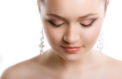 Närbildstående av en ung flicka med en bröllopmakeup Perfekt hud, slätt hår, stora crystal örhängen och hårprydnad Isolator Royaltyfria Bilder