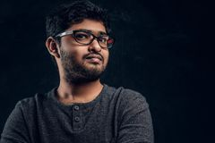 Närbildstående av en ung indisk grabb i eyewearen och tillfällig kläder som ser en kamera i studio royaltyfri fotografi