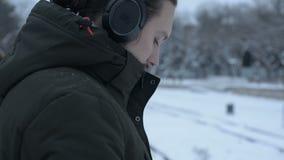 Närbildstående av en ung långhårig man med ett skägg i hörlurar som står på ett spårvagnstopp, i vinter och att vänta stock video
