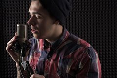 Närbildstående av en ung man som sjunger med hans ögon som stängs i ett lock som framme står av mikrofonställningen som rymmer ha Arkivbilder