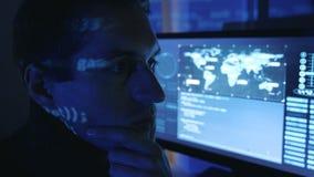 Närbildstående av en yrkesmässig bärareprogrammerare för man i en datorhall som fylls med bildskärmskärmar En hackerarbeten arkivfilmer
