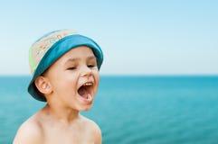 Närbildstående av ett gulligt som ler unga barnet på stranden Folk, lopp, ferier och turismbegrepp Royaltyfria Foton