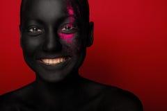 Närbildstående av kvinnan i svart målarfärg arkivbild