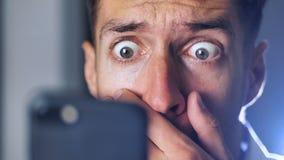 Närbildstående av läsande oväntad nyheterna för förvånad man på hans smarta telefon arkivfilmer