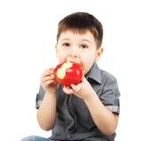 Närbildstående av lite pojken som äter det röda äpplet Arkivfoto