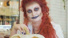Närbildstående av rödhårig mankvinnan med halloween makeup med pumpa royaltyfri bild