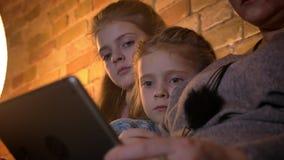 Närbildstående av två gulliga lilla caucasian flickor som uppmärksamt håller ögonen på in i minnestavlan i mysig hem- atmosfär stock video