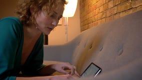 Närbildstående i profil av den ljust rödbrun lockig-haired caucasian flickan som ligger på soffan och skriver på minnestavlan på  stock video
