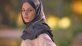 Närbildstående i profil av den muslimska flickan, i kamera och att hålla ögonen på för nolla för hijab vändande allvarligt arkivfilmer