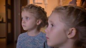Närbildstående i profil av små caucasian flickor som uppmärksamt håller ögonen på film i mysig hem- atmosfär stock video