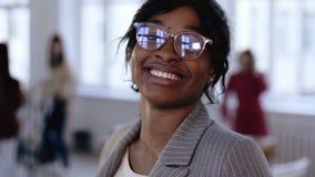 Närbildstående, positiv härlig ung afrikansk kvinna för kontorsanställd i glasögon som ler på det moderna vindkontoret stock video