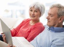 Närbilden av en pensionär kopplar ihop genom att använda bärbar dator Arkivfoton