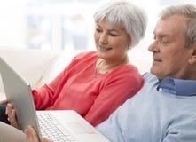 Närbilden av en pensionär kopplar ihop genom att använda bärbar dator Arkivbild