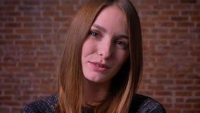 Närbildståenden av den caucasian ljust rödbrun kvinnan i hänglsen blinkar trevligt på kameraans-leenden bricken på bakgrund arkivfilmer