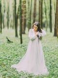 Närbildståenden av den härliga kvinnan i den vita bröllopsklänningen som ser jordningen och in sorterar hennes hår arkivfoto