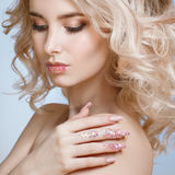 Närbildståenden av den härliga lockiga blondy kvinnan med perfekt konstsmink, moderiktigt frostat spikar design med blänker Fotografering för Bildbyråer