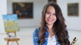 Närbildståenden av den le flickan som trycker på hennes hår med målning, borstar 4K stock video