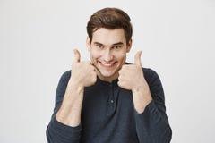 Närbildståenden av den roliga unga grabben med lyckligt och kusligt uttryck som visar tummar upp near framsida, medan stå över Fotografering för Bildbyråer