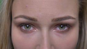 Närbildståenden av den unga blonda modemodellen lyfter hennes ögon och klockor allvarligt och fast beslutsamt in i kamera arkivfilmer
