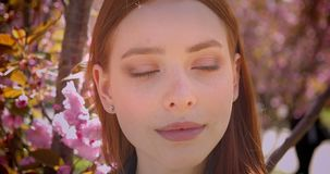 Närbildståenden av den ursnygga ljust rödbrun flickan som håller ögonen på med lugna leende in i kamera på rosa blom-, parkerar b lager videofilmer