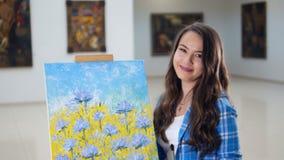 Närbildståenden av flickaanseendet nära målningen 4K lager videofilmer