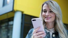 Närbildståenden av kvinnan i staden använder den utomhus- smartphonen Nätt hipster, studentflicka som smsar på och använder appen stock video